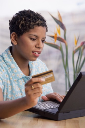 Woman operating a laptop holding a credit card : Stock Photo