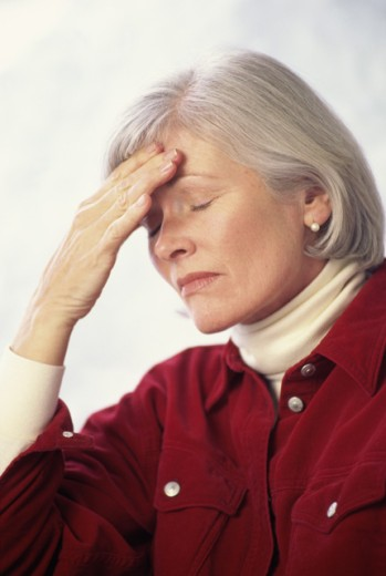 Stock Photo: 1574R-09557B Woman holding her forehead in pain