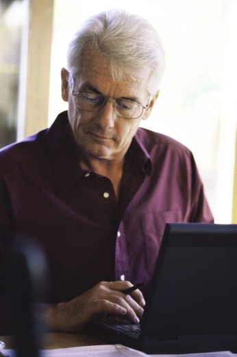 Stock Photo: 1574R-09617 Senior man using a laptop