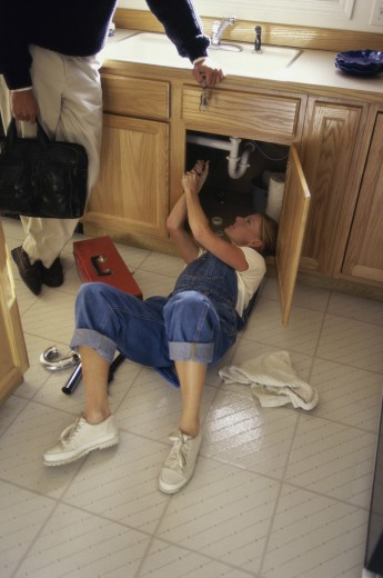 Stock Photo: 1574R-09659 Young woman repairing the plumbing under a kitchen sink