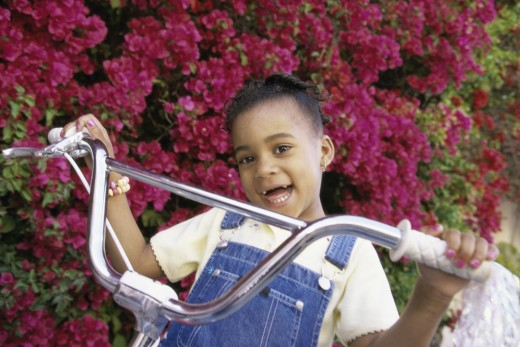 Portrait of a girl holding the handlebars of a bicycle : Stock Photo