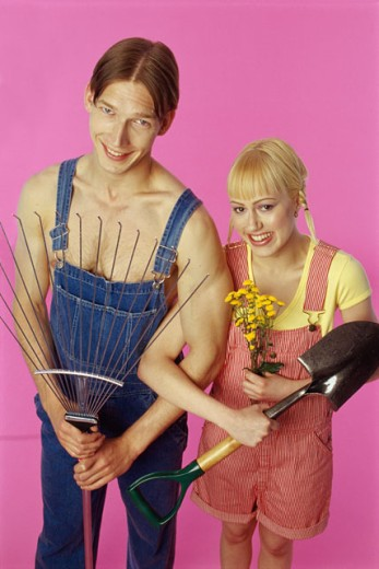 Portrait of a teenage couple holding a rake and a shovel : Stock Photo