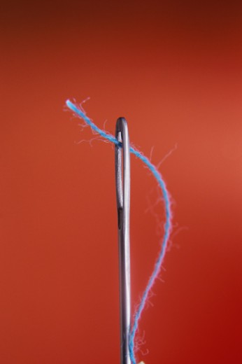 Close-up of thread through the eye of a needle : Stock Photo