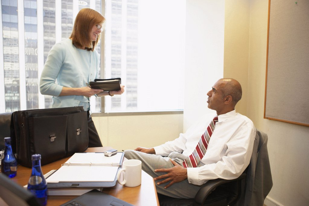 Stock Photo: 1574R-20156 Businessman talking to his secretary in an office