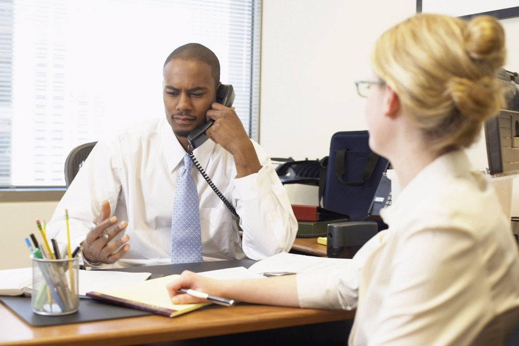 Stock Photo: 1574R-20211 Businessman talking on the telephone with his secretary sitting in front of him