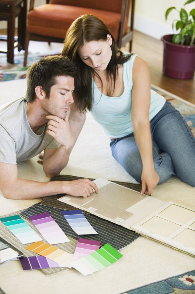 High angle view of a young couple with color swatches in front of them : Stock Photo