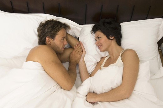 High angle view of a young couple lying in the bed and smiling : Stock Photo