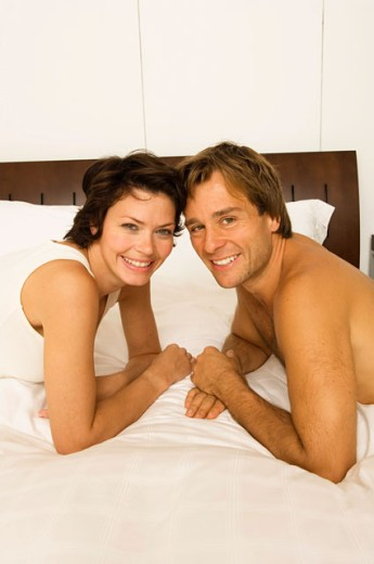 Portrait of a young couple lying in the bed and smiling : Stock Photo