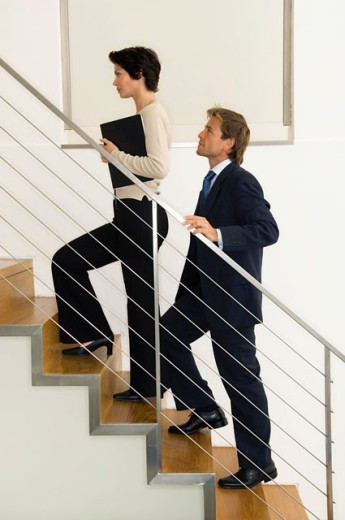 Stock Photo: 1574R-20388 Side profile of a businesswoman climbing up stairs with a businessman