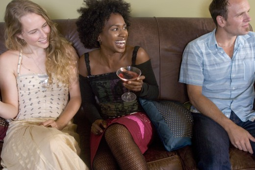 Close-up of two young women and a young man sitting on a couch at a party : Stock Photo