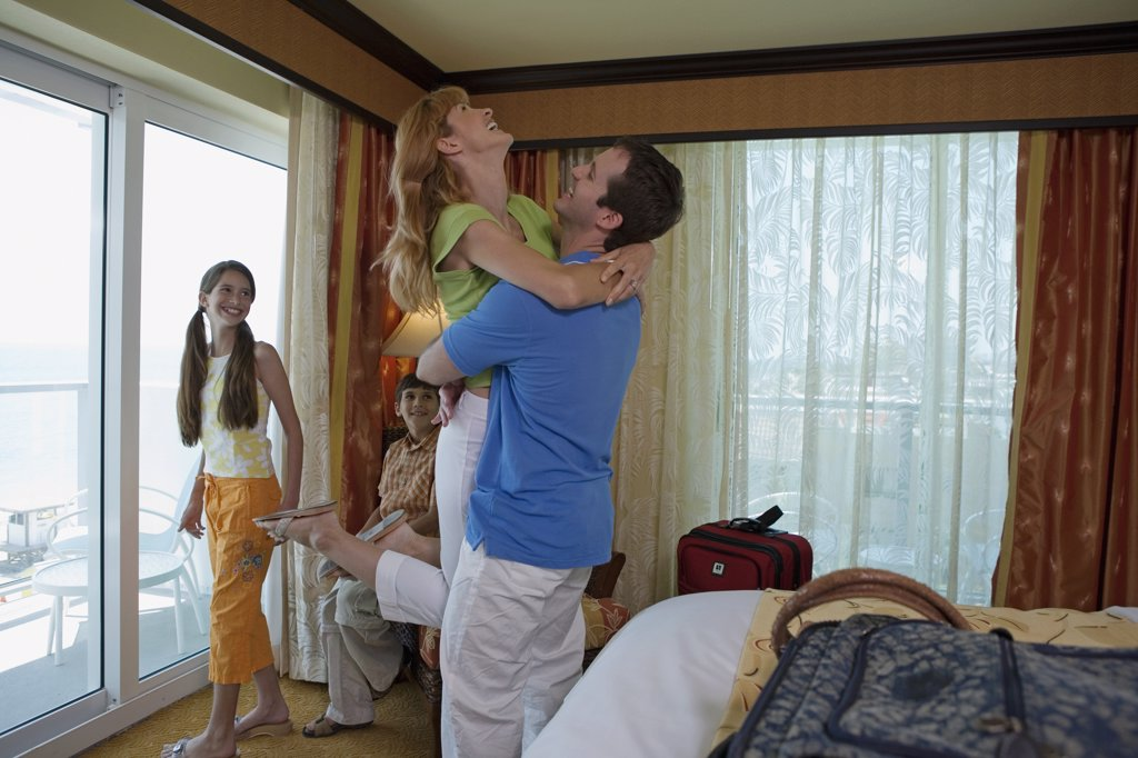 Side profile of a young couple with their son and daughter in a hotel room : Stock Photo