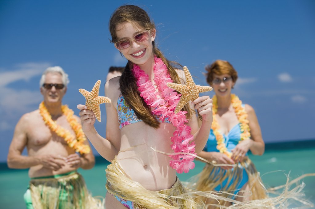 Close-up of a girl holding two starfish with her grandparents standing behind her on the beach : Stock Photo