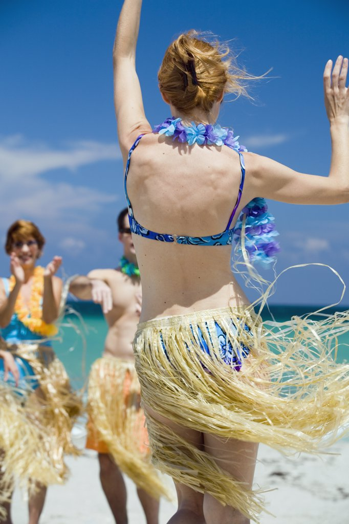 Rear view of a young woman hula dancing on the beach : Stock Photo