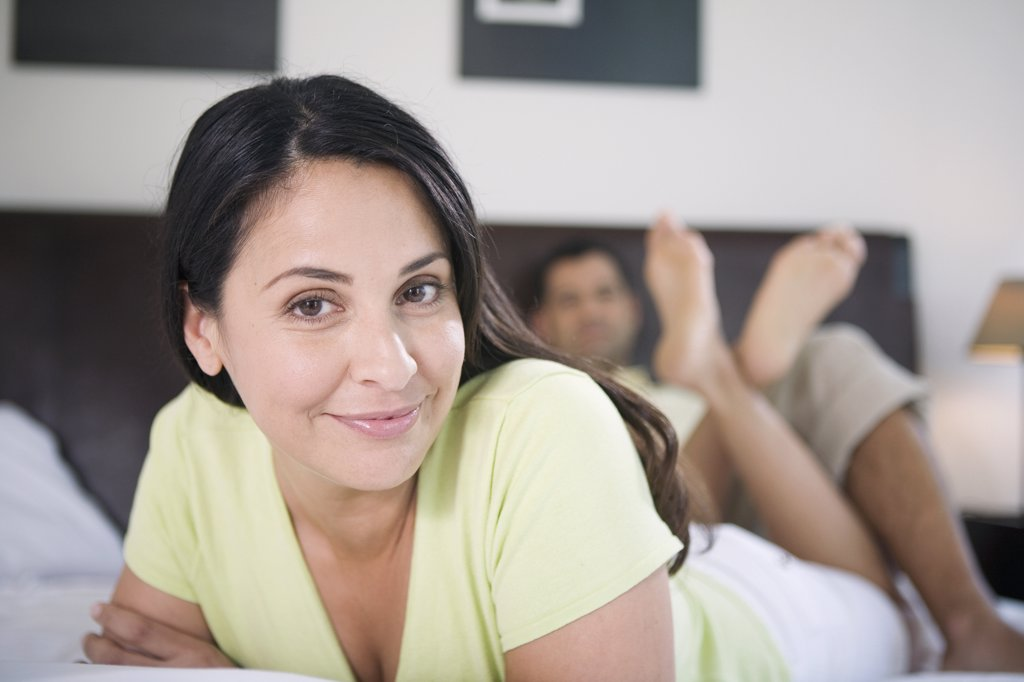 Portrait of a mature woman lying in the bed with a mature man reclining behind her : Stock Photo