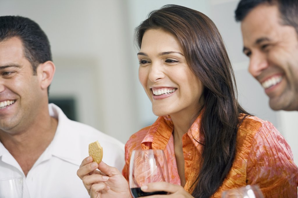 Close-up of a mid adult woman with a mature man and a mid adult man smiling : Stock Photo