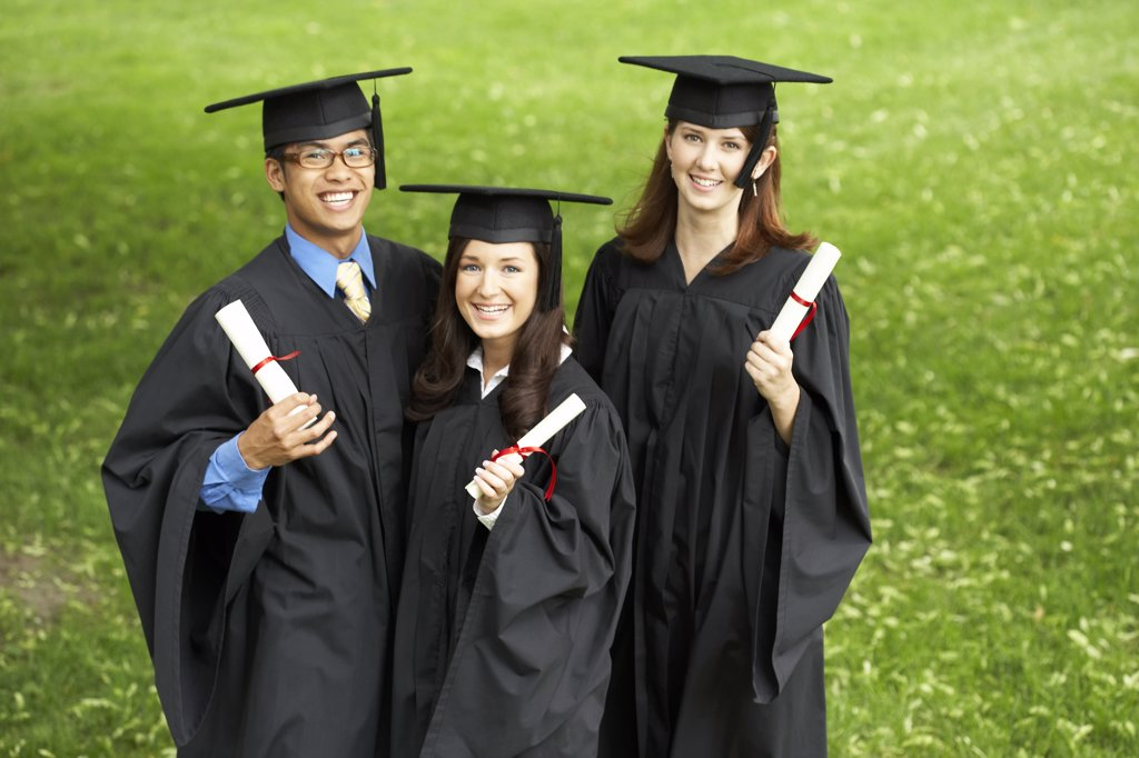 Stock Photo: 1574R-20927 Two female graduates and a male graduate holding diplomas