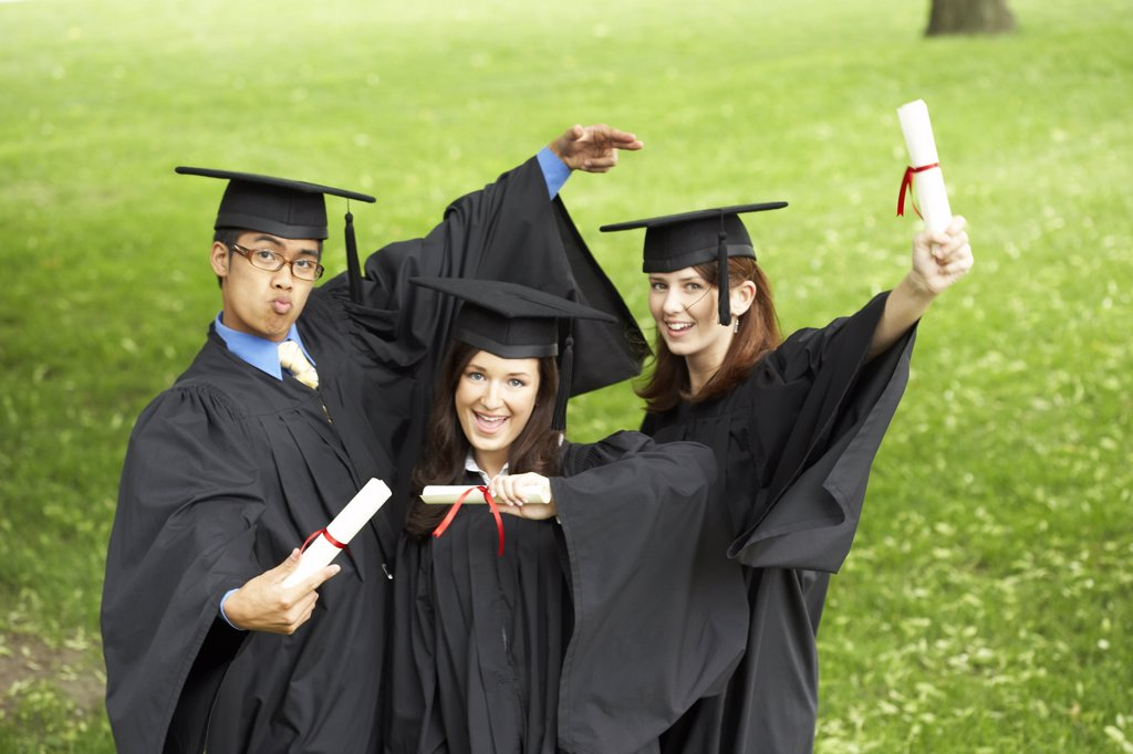 Two female graduates and a male graduate holding diplomas : Stock Photo