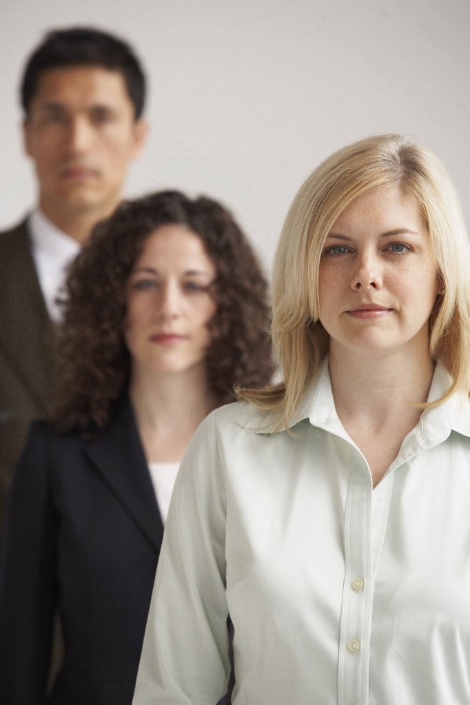 Portrait of two businesswomen and a businessman standing in a row : Stock Photo
