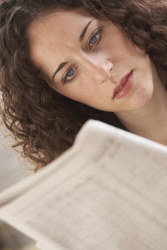Close-up of a businesswoman reading a newspaper : Stock Photo