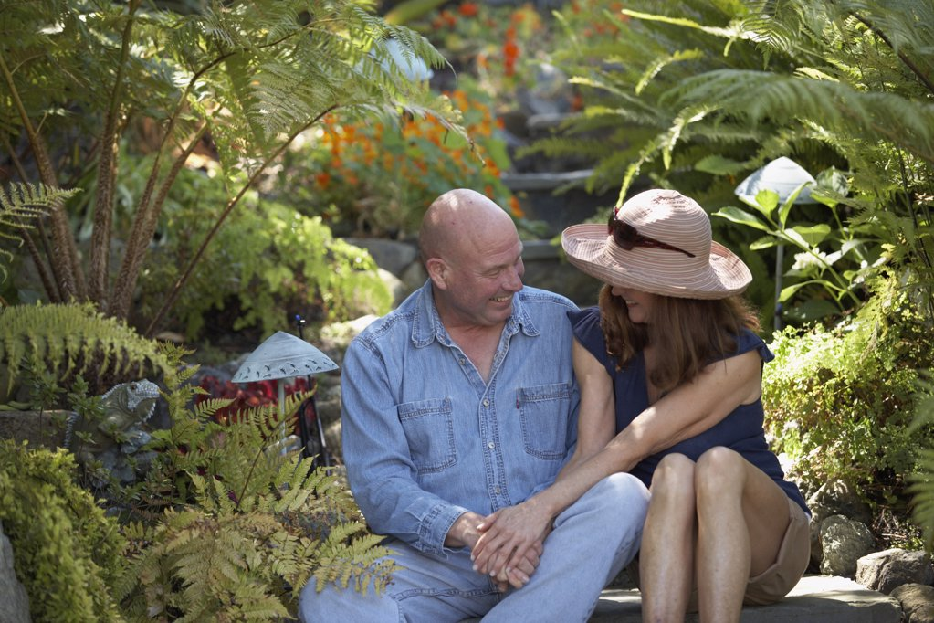 Close-up of a mature couple sitting in a garden and looking at each other : Stock Photo