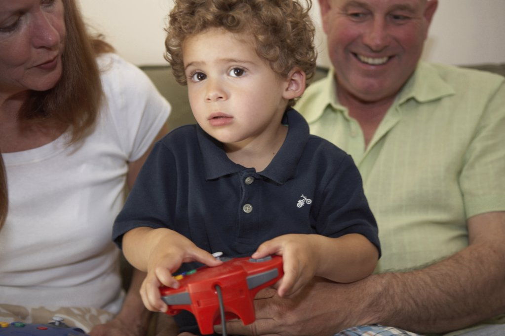Close-up of a boy sitting with his grandparents and playing a video game : Stock Photo