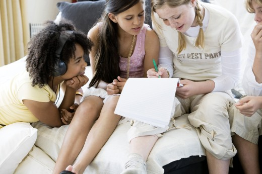 Stock Photo: 1574R-21175 High angle view of a girl writing on a notepad with her friends sitting beside her