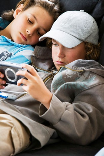 Stock Photo: 1574R-21192B Close-up of a boy playing a handheld video game with another boy lying beside him
