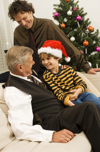 Side profile of a senior man with his son and grandson sitting on a couch : Stock Photo