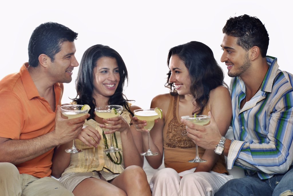 Stock Photo: 1574R-21435 Mid adult couple and a young couple sitting on a couch and holding margaritas