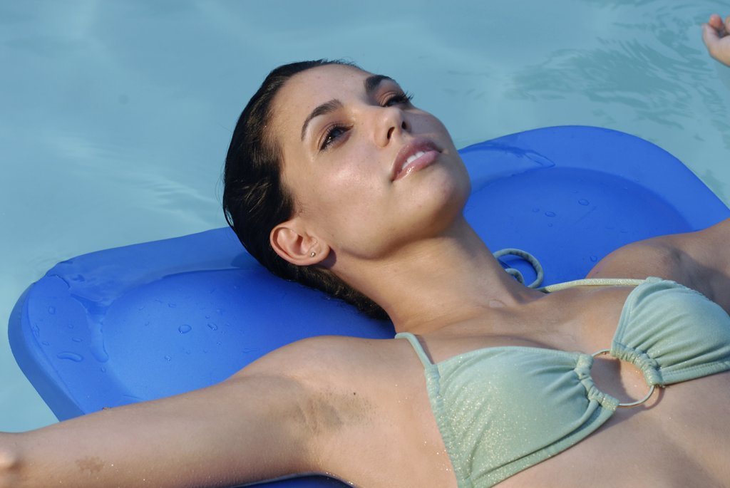 Close-up of a young woman lying on a pool raft in a swimming pool : Stock Photo