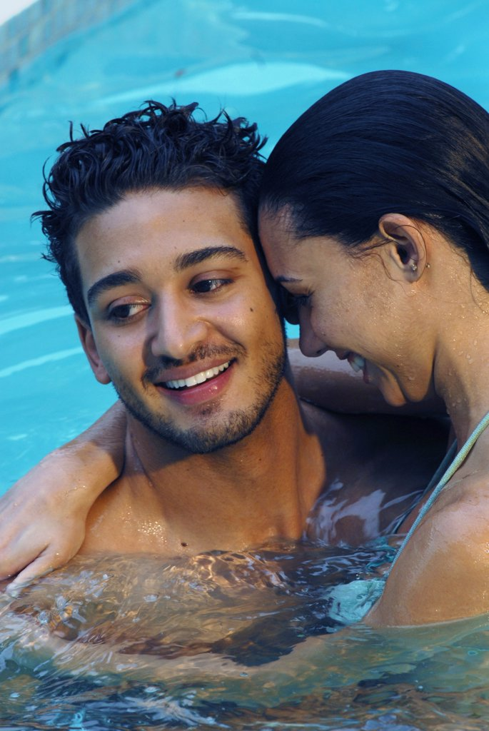 Close-up of a young couple embracing each other in a swimming pool : Stock Photo