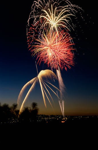 Low angle view of fireworks display at night in a city : Stock Photo