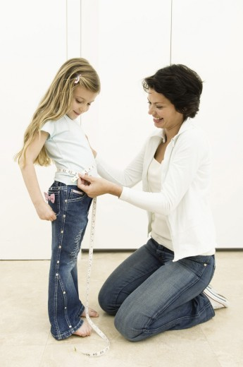 Stock Photo: 1574R-24883 Side profile of a young woman measuring the waist of her daughter with a tape measure