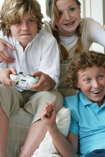 Stock Photo: 1574R-24897 Close-up of a boy playing a video game with his friends
