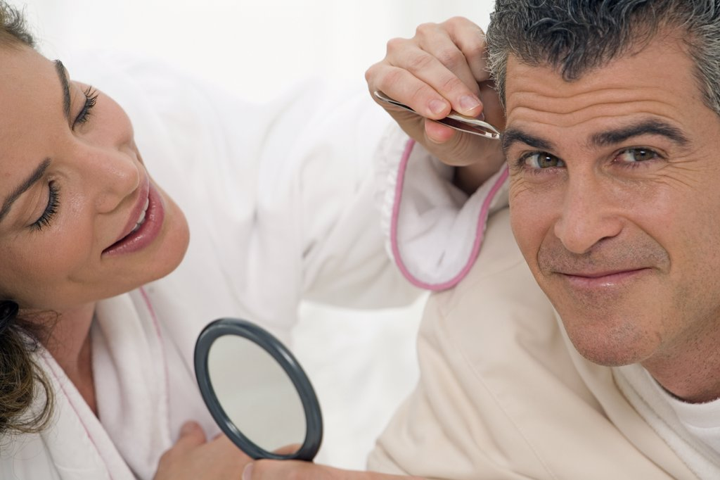 Stock Photo: 1574R-25023 Mid adult woman plucking the eyebrows of a mature man