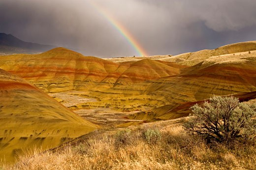Rainbow over hills, Painted Hills, John Day Fossil Beds National Monument, Oregon, USA : Stock Photo