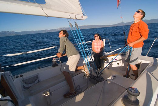Two young men and a young woman on a sailboat : Stock Photo