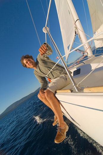 Young man sitting on the edge of a sailboat and smiling : Stock Photo