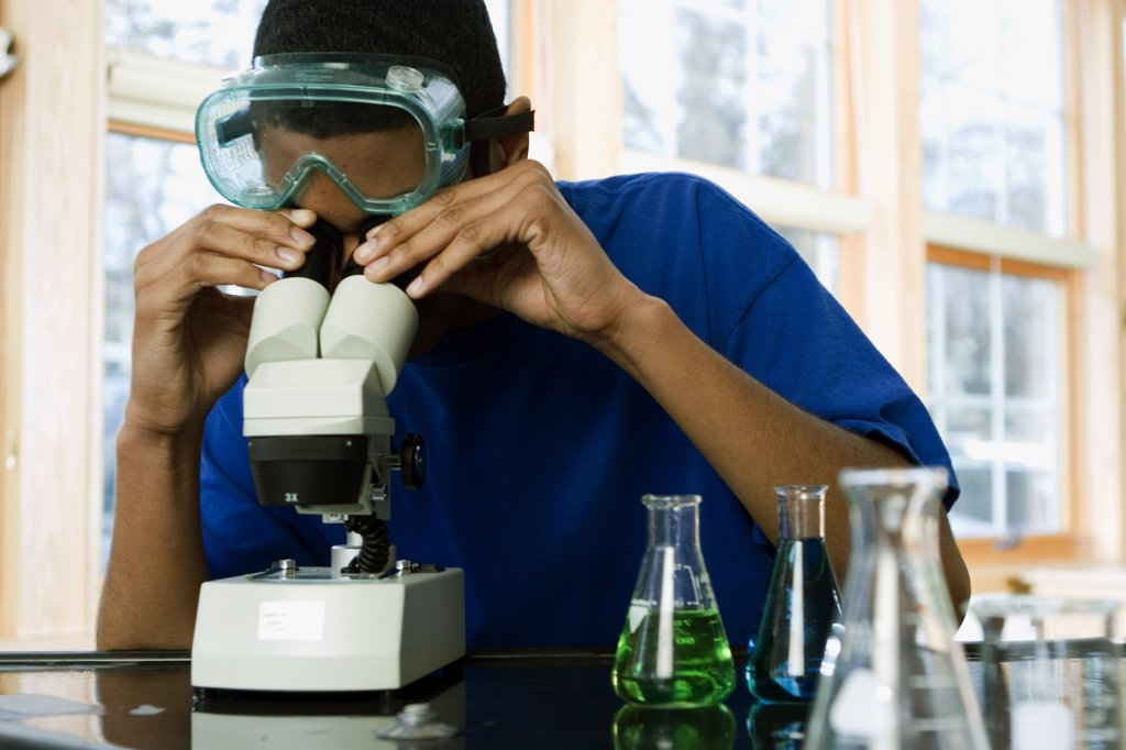 Student looking through a microscope in a science lab : Stock Photo