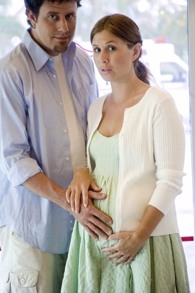 Stock Photo: 1574R-25600 Mid adult man touching the abdomen of a pregnant young woman