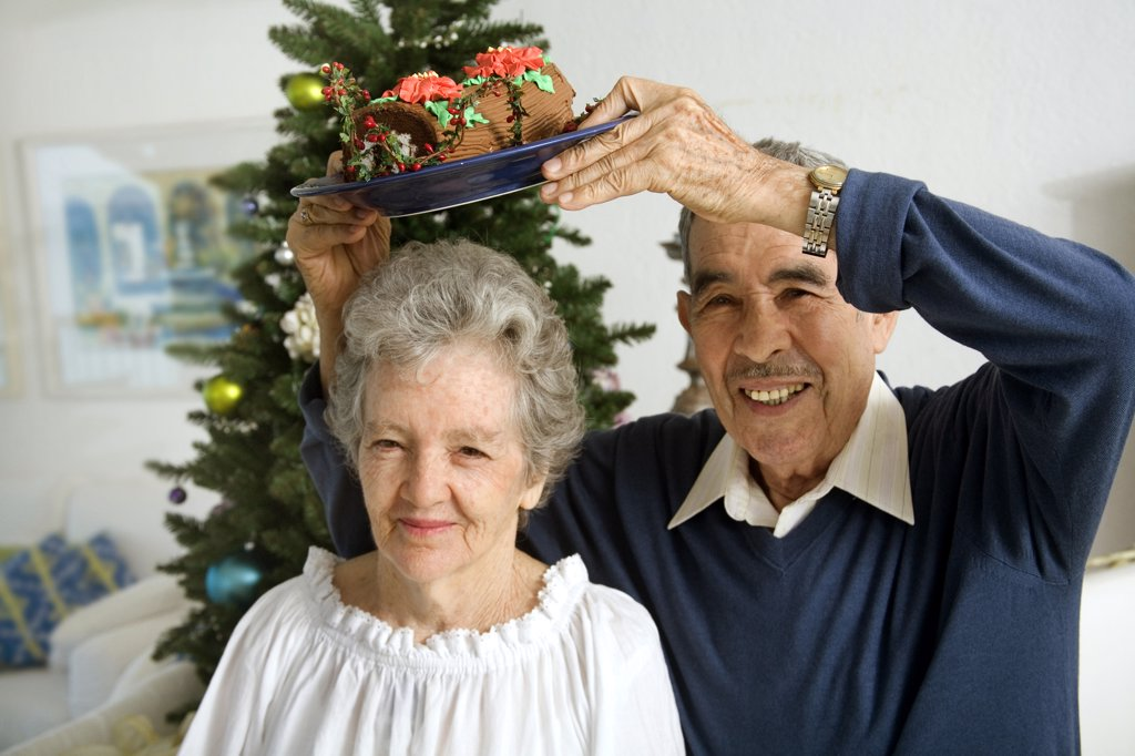 Stock Photo: 1574R-25982 Portrait of a senior man holding a plate of Yule log shaped cake over a senior woman's head