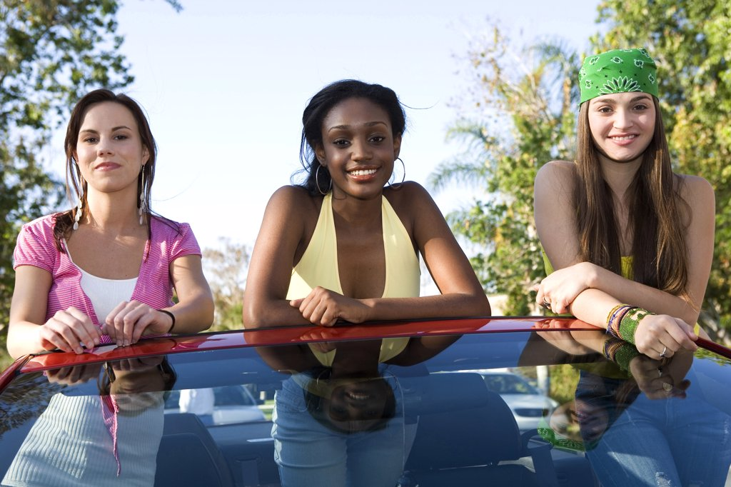 Two teenage girls and a young woman leaning on a car windshield : Stock Photo