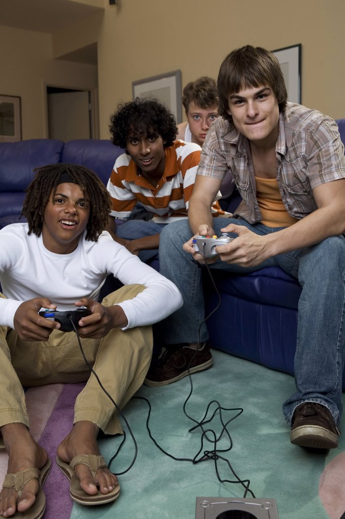 Teenage boy and a young man playing a video game : Stock Photo