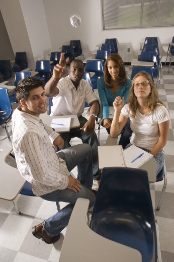 Portrait of university students in the classroom while one student throwing paper : Stock Photo
