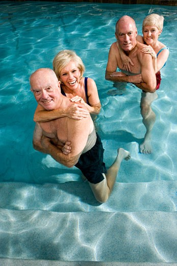 Stock Photo: 1574R-27372 Portrait of cheerful senior couples embracing in swimming pool