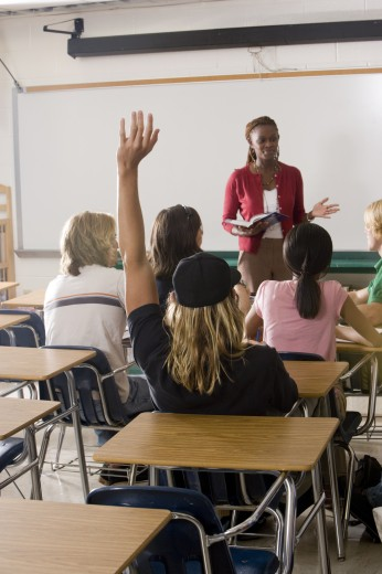 Stock Photo: 1574R-27652 Female teacher holding book and student raising hands in the classroom