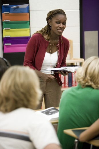 Cheerful female teacher teaching students in the classroom : Stock Photo