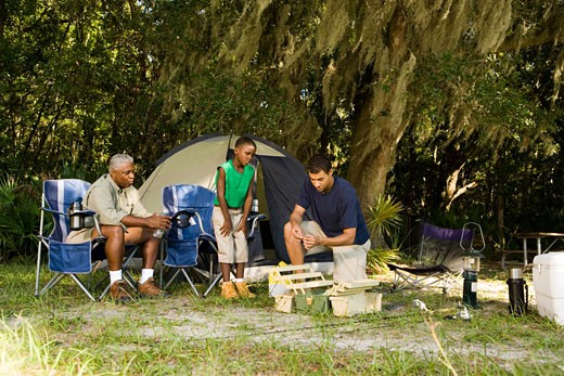 Stock Photo: 1574R-27897 Mature man with his son and friend by tent at forest