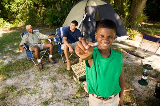 Portrait of a boy holding bait hook while men discussing by tent at forest : Stock Photo