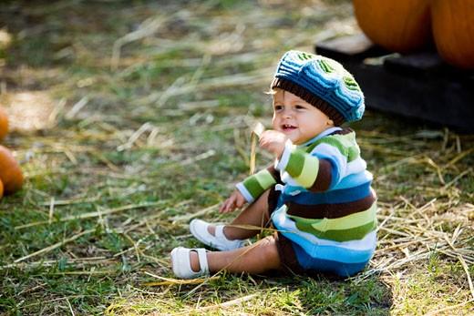 Cute boy in warm clothing sitting on hay : Stock Photo